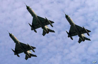 Indian Air Force MIG 21 jet fighters perform during a parade at an airbase in Tezpur, India, Nov. 21 2014.