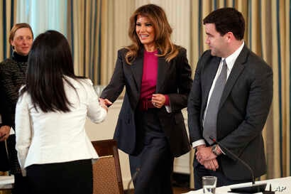 First lady Melania Trump speaks with Snap Director of Public Policy Jennifer Park Stout, left, and Twitter Director of Public Policy Carlos Monje, right, as she arrives for roundtable discussion on cyberbullying, in the State Dining Room of the White...