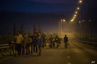Syrian refugees walk along a road of the border town of Idomeni , northern Greece, to cross the border and enter Macedonia, Aug. 25, 2015.