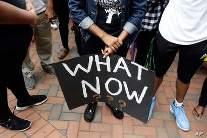 Students at the University of North Carolina-Charlotte hold a vigil following Tuesday's police shooting of Keith Lamont Scott at The Village at College Downs apartment complex in Charlotte, N.C., Sept. 21, 2016.