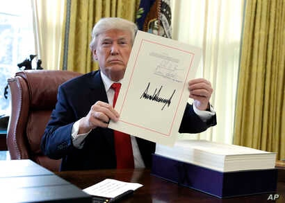 President Donald Trump displays the $1.5 trillion tax overhaul package he had just signed, Friday, Dec. 22, 2017.