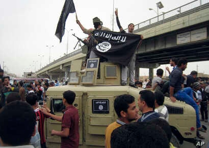 FILE - Islamic State group militants hold up their flag as they patrol in a commandeered Iraqi military vehicle in Fallujah, Iraq, March 30, 2014. The United States Friday sanctioned three members of the Islamic State who were featured in a beheading...