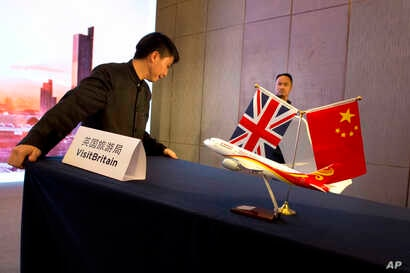 FILE - Staff workers prepare for a signing ceremony by British officials with China's Hainan Airlines Group to develop new flight routes to encourage Chinese tourists to Britain in Beijing, China, May 18, 2016.