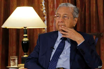 Malaysia's Prime Minister Mahathir Mohamad listens during an interview with The Associated Press in Putrajaya, Malaysia, Aug. 13, 2018.