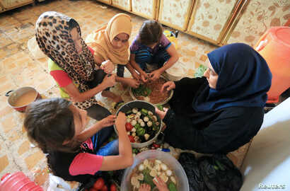 FILE - Sana Ibrahim al-Taee, 64, prepares food with some of her grandchildren at her home in Mosul, Iraq, July 30, 2018