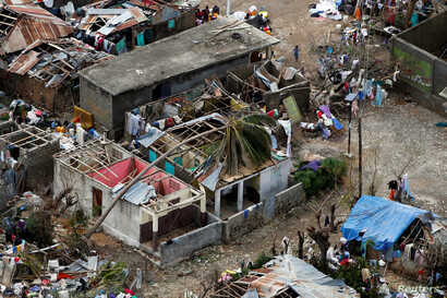 People stand next to destroyed houses after Hurricane Matthew passed Jeremie, Haiti, Oct. 6, 2016.