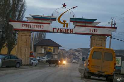 """An entrance to the village of Gubden with a sign reading """"Happy Travel. Gulden"""" is decorated with banner in colors of Russian and Dagestani flags,  in the village of Gubden, Dagestan, Russia, Nov. 15, 2015."""