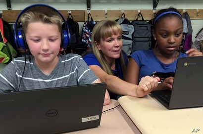 FILE - Fifth grade teacher Heather Dalton, center, works with students Julian Ryno, left, and Ma'Kenley Burns, doing math problems on the DreamBox system at Charles Barnum Elementary School in Groton, Connecticut, Sept. 20, 2018.