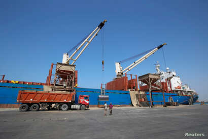 FILE - Workers unload aid shipments of wheat from St. George ship, at the Red Sea port of Hodeidah, Yemen, Nov. 30, 2017.