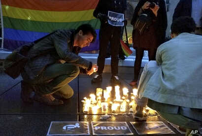 A man lights a candle during a spontaneous  vigil to remember those slain and wounded at an Orlando nightclub, in Paris, France, June 12, 2016.