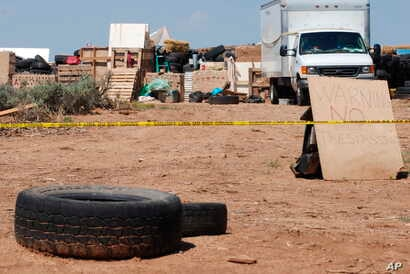 Police tape restricts access to a disheveled living compound in Amalia, N.M., Aug. 7, 2018.
