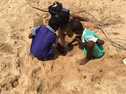 School children trap water from a dry river in Masvingo district – about 300km south of Harare, Dec. 29, 2017.