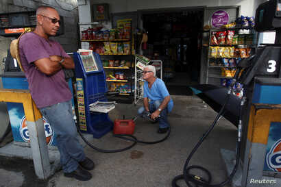 Men buy gasoline, after Hurricane Maria hit the island in September 2017, in Maunabo, Puerto Rico, Jan. 27, 2018.