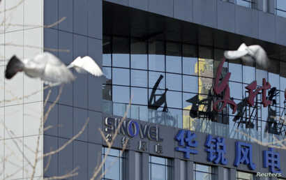 FILE - Birds fly past the company logo of Sinovel Wind Co. Ltd. outside its head office in Beijing, Jan. 6, 2011.