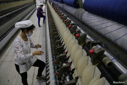 FILE - A worker disentangles wool yarn at a spinning machine at a factory owned by Hong Kong's Novetex Textiles Limited in Zhuhai City, Guangdong province, China, Dec. 13, 2016.  Novetex is set to open a factory in Hong Kong that will use new technol...