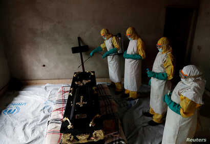 A healthcare worker sprays a room during a funeral of  Kavugho Cindi Dorcas who is suspected of dying of Ebola in Beni, North Kivu Province of Democratic Republic of Congo, December 9, 2018.