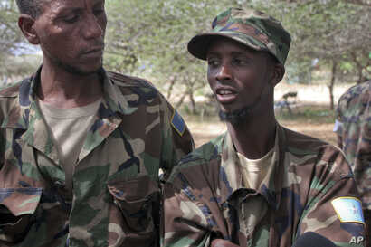 FILE - Mohamed Abdi Abdullahi, left, and Abshir Ali Mohamed, both defectors from the Somali militant group al-Shabab who became fighters with Somali government forces alongside the African Union peacekeeping force, speak to reporters at the AU base i...