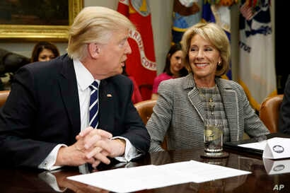 FILE - President Donald Trump talks to Education Secretary Betsy DeVos in the Roosevelt Room of the White House in Washington, Feb. 14, 2017.