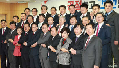 Lawmakers defecting from the ruling Saenuri Party pose for photographs during a news conference at the National Assembly in Seoul, South Korea, Dec. 27, 2016.