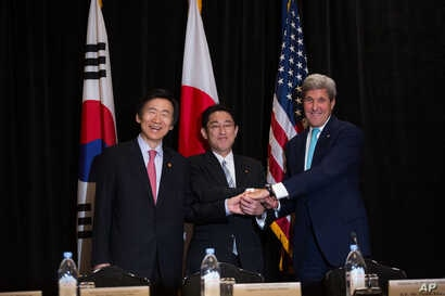 Minister of Foreign Affairs Yun Byung-se of South Korea, left, Minister of Foreign Affairs Fumio Kishida of Japan, and U.S. Secretary of State John Kerry join hands during a meeting between the three leaders Sunday, Sept. 18, 2016, in New York .