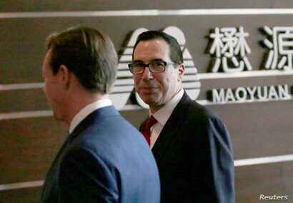 U.S. Treasury Secretary Steven Mnuchin, right, and a U.S. delegation arrive at a hotel in Beijing for trade talks with China, May 3, 2018.