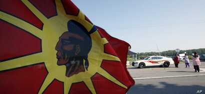 A law enforcement officer passes a tax protest on the Tuscarora Indian Nation in New York, Wednesday, Sept. 1, 2010. A federal judge had temporarily blocked New York state's plans to tax cigarette sales by two Native American Nations to non-Native cu...