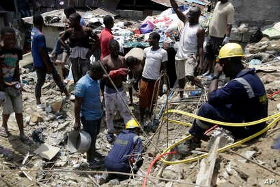Emergency services attend the scene after a building collapsed in Lagos, Nigeria, March 13, 2019.