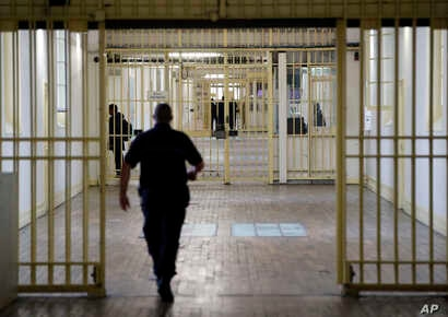 FILE - A guard walks in the corridor of Fresnes prison, south of Paris, France, Sept. 20, 2016.