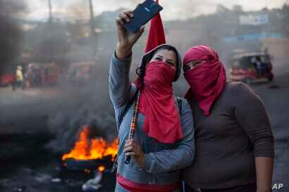 Masked supporters of presidential candidate Salvador Nasralla take a selfie at a burning roadblock set up by demonstrators protesting what they call electoral fraud in Tegucigalpa, Honduras, Dec. 1, 2017.