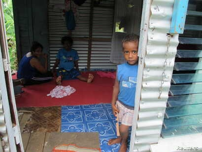 Rusiate, the 3-year-old son of Laisiasa Caukiuai, the headman of Tutua, a village on Fiji's Koro island, peers out the door of a tin-sided house owned by family members in Suva, Fiji's capital, Feb. 9, 2018.