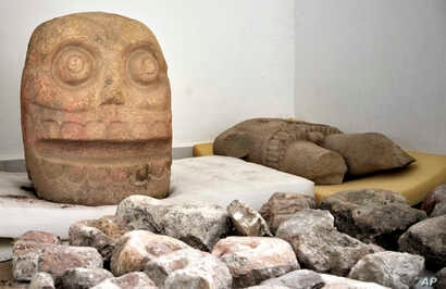 A skull-like stone carving and a stone trunk depicting the Flayed Lord are stored after being excavated from the Ndachjian–Tehuacan archaeological site in Tehuacan, Puebla state in this 2018 photo provided by Mexico's National Institute of Anthropo...