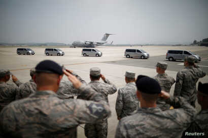 U.S. soldiers salute vehicles transporting the remains of 55 U.S. soldiers who were killed in the Korean War at Osan Air Base in Pyeongtaek, South Korea, July 27, 2018.