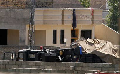 Vehicles are parked inside the compound of a house where it is believed  bin Laden lived in Abbottabad, Pakistan.