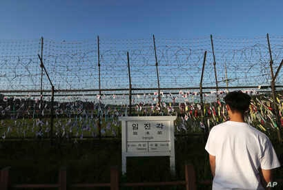 A man walks by the wire fences adorned with national flags near an information sign showing the distance to North Korea's Kaesong city and South Korea's capital, Seoul, at the Imjingak Pavilion in Paju, South Korea, Sept. 15, 2017. North Korea conduc...