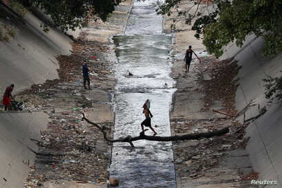 A local carries a water container as he crosses a river in Caracas, Venezuela, March 12, 2019.