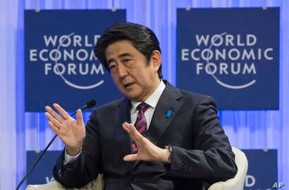 Japanese Prime Minister Shinzo Abe gestures as he speaks at the World Economic Forum in Davos, Switzerland, Wednesday, Jan. 22, 2014.