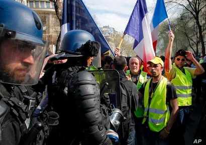"Riot police stand by as French ""yellow vest"" protesters rally, March 30, 2019, in Paris. The demonstrators are undeterred by protest bans or repeated injuries in 20 weeks of demonstrations."