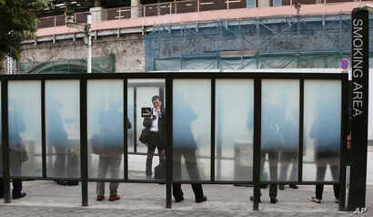 FILE - People are seen gathered at a smoking area in Tokyo, Japan, April 7, 2017.
