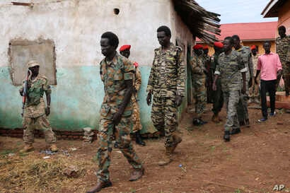 FILE -South Sudanese soldiers accused of a horrific attack on foreign aid workers including rape, torture, killing and looting on the Terrain hotel compound, are assisted to a prison van after attending their trial in Juba, South Sudan.