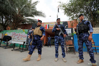 Iraqi security forces stand guard outside a polling station during the parliamentary election in the Sadr city district of Baghdad, May 12, 2018.