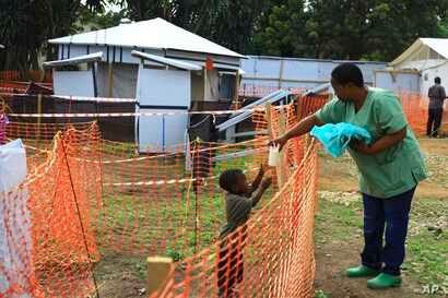 In this photo taken Sept 9, 2018, a health worker, right, feeds a boy suspecting of having the Ebola virus at an Ebola treatment centre in Beni, Eastern Congo.