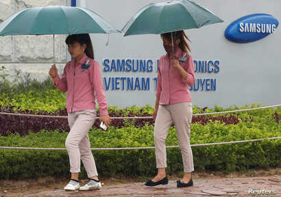 An employee (L) holds a smartphone as she is on the way to work at the Samsung factory in Thai Nguyen province, north of Hanoi, Vietnam October 13, 2016.
