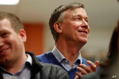 FILE - Former Colorado Gov. John Hickenlooper waits to speak at the Story County Democrats' annual soup supper fundraiser, Feb. 23, 2019, in Ames, Iowa.