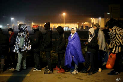 """Migrants wait to register outside a processing center in the makeshift migrant camp known as """"the jungle"""" near Calais, northern France, Oct. 26, 2016."""