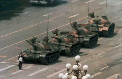 FILE - A Chinese man stands alone to block a line of tanks heading east on Beijing's Cangan Boulevard in Tiananmen Square, June 5, 1989.