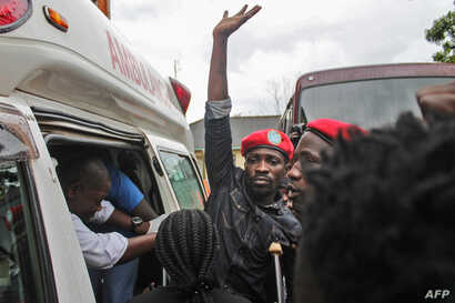 Ugandan singer-turned-politician Robert Kyagulanyi, center, better known as Bobi Wine, reacts as he gets into an ambulance after being released on bail at the High Court in Gulu, northern Uganda, Aug. 27, 2018.