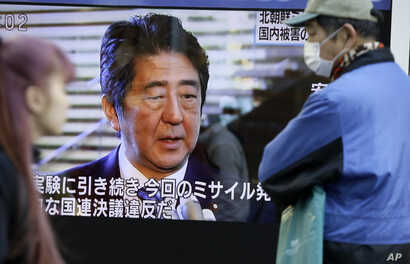 Passers-by look at a TV screen showing Japanese Prime Minister Shinzo Abe speak on North Korea's rocket launch, in Tokyo, Feb. 7, 2016.