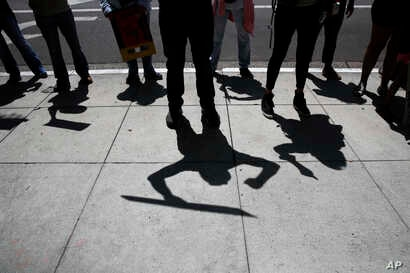 Protesters cast their shadows as they chant slogans during a rally outside the the Millennium Biltmore Hotel in Los Angeles where Attorney General Jeff Sessions was scheduled to speak, June 26, 2018.