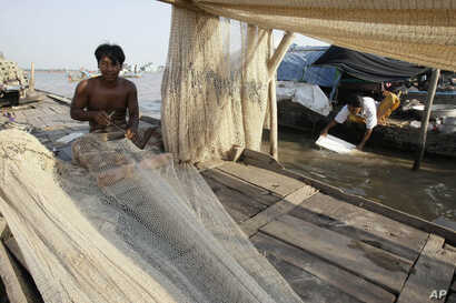 FILE - A Cambodian man fixes his fishing nets during the dry season on the Mekong river bank, Feb. 28, 2012