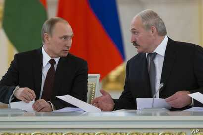 FILE - Russian President Vladimir Putin, left, and visiting Belarus' counterpart Alexander Lukashenko speak to each other a meeting in Moscow's Kremlin, Russia, Dec. 25, 2013.